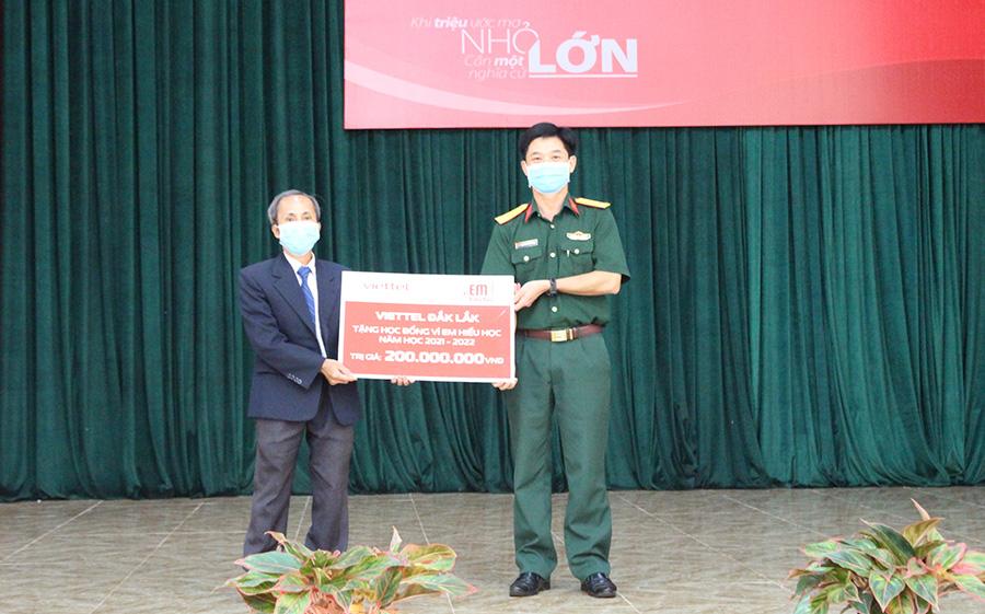 Đại diện Viettel Đắk Lắk trao biểu trưng số tiền học bổng tặng các em học sinh huyện Lắk.
