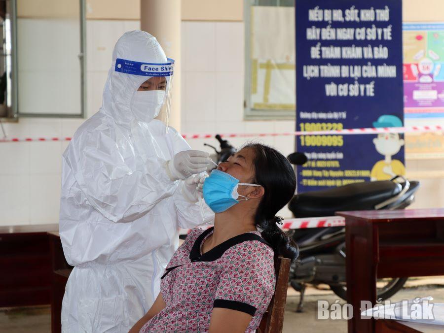 Nhân viên y tế lấy mẫu xét nghiệm SARS-CoV-2 cho người dân tại Trạm Y tế phường Tân Thành.