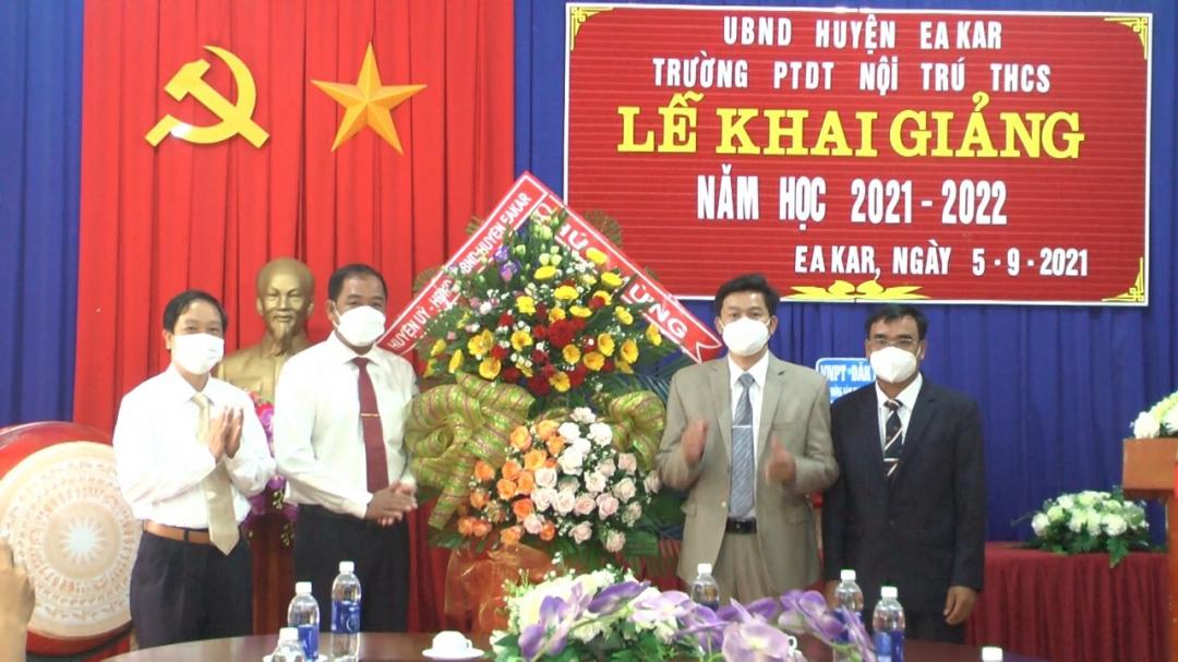 Bí thư Huyện ủy Ea Kar Y Nhuân Bjă (thứ hai bên trái) cùng lãnh đạo Phòng GD-ĐT tặng hoa chúc mừng Trường PTDT nội trú THCS huyện nhân dịp khia giảng năm học mới. Ảnh: Nguyễn Xuân