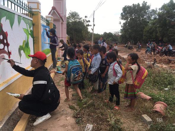 Các em nhỏ ở xã Cư Kbang (huyện Ea Súp) thích thú với những bức tranh tường mới lạ do nhóm vẽ của Kim Anh thực hiện.