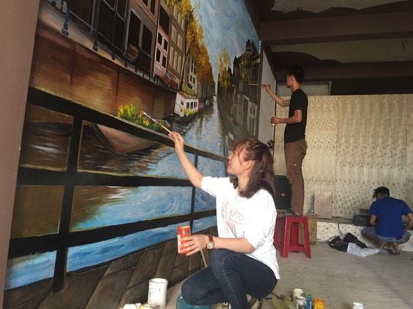 Kim Anh cùng nhóm vẽ thực hiện tác phẩm của mình tại huyện Cư Kuin.